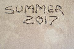 Word de zomer van 2017 wordt geschreven op een zandige oppervlakte Royalty-vrije Stock Afbeelding