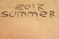 Word 2017 de zomer wordt geschreven op een zandige oppervlakte Stock Foto