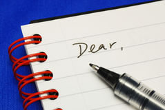 The word Dear with a pen. Concepts of writing a letter isolated on blue stock photography