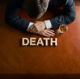 Word Death and devastated man composition. Word Death made of wooden block letters and devastated middle aged caucasian man in a black suit sitting at the table royalty free stock image