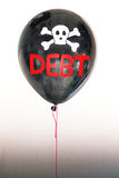 The word debt in red and a skull and cross bones on a balloon illustrating the concept of a debt bubble Royalty Free Stock Photos