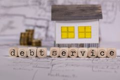 Word DEBT SERVICE composed of wooden letter. Small paper house in the background. Closeup stock photos