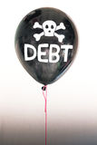 The word debt in white and a skull and cross bones on a balloon illustrating the concept of a debt bubble Royalty Free Stock Images
