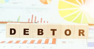 Free Word Debtor With Black Letters On Wooden Blocks On Table Stock Photography - 185136222