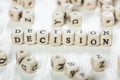 Decision word written on wood block. Word DECISION formed by wood alphabet blocks. On old wooden table Royalty Free Stock Photo