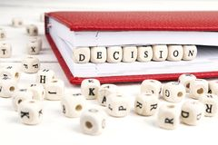Word Decision written in wooden blocks in red notebook on white. Wooden table. Wooden abc Royalty Free Stock Images