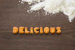 Word DELICIOUS Alphabet Biscuits on wood desk Royalty Free Stock Photos