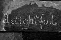 The word delightful written with chalk on black stone Royalty Free Stock Images