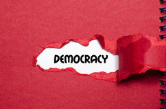 The word democracy appearing behind torn paper. The word democracy behind torn paper stock images