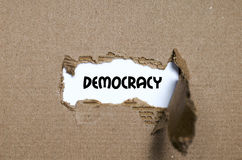 The word democracy appearing behind torn paper. The word democracy behind torn paper royalty free stock photo