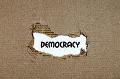 The word democracy appearing behind torn paper. The word democracy behind torn paper stock image