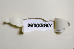 The word democracy appearing behind torn paper. The word democracy behind torn paper royalty free stock image