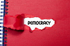 The word democracy appearing behind torn paper. The word democracy behind torn paper royalty free stock photos