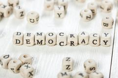 Democracy word written on wood block. Word DEMOCRACY formed by wood alphabet blocks. On old wooden table stock photos