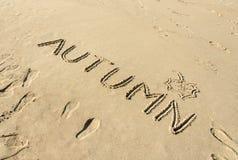 Word den handskrivna hösten och leafen som tecknas i sand Arkivbild