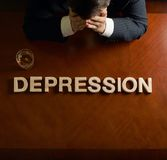 Word Depression and devastated man composition. Word Depression made of wooden block letters and devastated middle aged caucasian man in a black suit sitting at royalty free stock photo