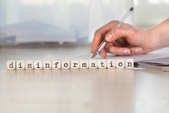 Word DESINFORMATIE uit houten brieven wordt samengesteld die royalty-vrije stock fotografie