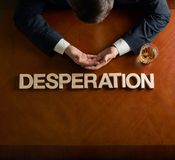 Word Desperation and devastated man composition. Word Desperation made of wooden block letters and devastated middle aged caucasian man in a black suit sitting stock images