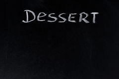 The word dessert written in chalk on a black board Stock Images