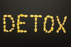 The word `detox` made from cornflakes on a black background royalty free stock images