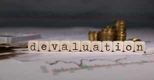 Word DEVALUATION composed of wooden letter. Stacks of coins in the background. Closeup royalty free stock photo