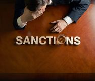 Word and devastated man composition. Word made of wooden block letters and devastated middle aged caucasian man in a black suit sitting at the table with the stock photos