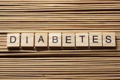 Word diabetes op houten kubussen bij houten achtergrond Stock Afbeeldingen