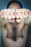 The word DIABETES written on the fists of a man Stock Image