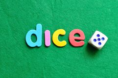 The word dice displayed with a dice. On a green background Stock Photos