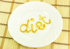 Word DIET on White Plate. Word DIET Baked Of Batter on White Plate on Bamboo Placemat Stock Photo