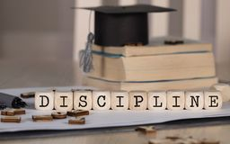 Word DISCIPLINE composed of wooden dices. Black graduate hat and books in the background. Closeup royalty free stock photo
