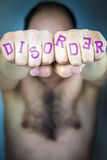 The word DISORDER written on the fists of a man Royalty Free Stock Photo