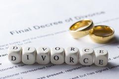Word - divorce composé des lettres en bois sur la table avec des anneaux de mariage Images stock