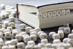 Word - divorce composé des lettres en bois sur la table avec des anneaux de mariage Images libres de droits