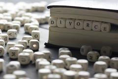 Word - divorce composé des lettres en bois sur la table avec des anneaux de mariage Image libre de droits