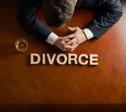 Word Divorce and devastated man composition. Word Divorce made of wooden block letters and devastated middle aged caucasian man in a black suit sitting at the royalty free stock photography