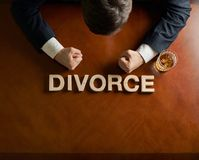 Word Divorce and devastated man composition. Word Divorce made of wooden block letters and devastated middle aged caucasian man in a black suit sitting at the stock images