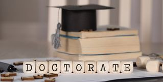 Word DOCTORATE composed of wooden dices. Black graduate hat and books in the background. Closeup stock photography