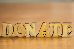 The word `donate` made of wooden letters royalty free stock images