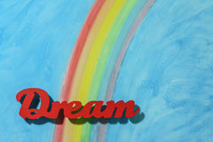 The word dream with a colorful rainbow and blue sky background Royalty Free Stock Image