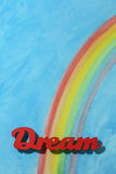 The word dream with a colorful rainbow and blue sky background Royalty Free Stock Photo