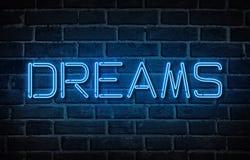 Word Dromen met neonbrieven bij bakstenen muurachtergrond die worden geschreven Royalty-vrije Stock Afbeelding