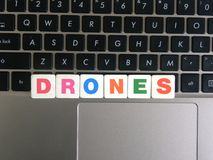 Word Drones on keyboard background.  stock images