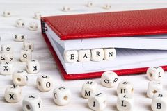 Word Earn written in wooden blocks in red notebook on white wood. En table. Wooden abc Royalty Free Stock Image