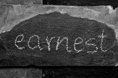 The word EARNEST written with chalk on black stone Stock Photos