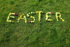 The word Easter spelt out in flowers. Easter is spelt out with primroses on a background of green grass. The flowers are predominantly yellow with some dark red Stock Images