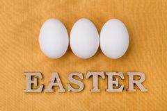 Word Easter, three white eggs on silk gold yellow background Royalty Free Stock Photo