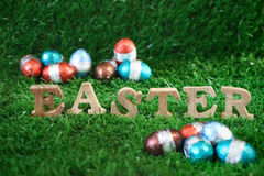 Word of Easter in wooden design with egg chocolate on the green grass, Royalty Free Stock Images