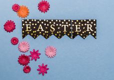 Easter background with copy space on blue paper. Word Easter written with golden letters on black pennant on blue paper and pink paper flowers and copy space Stock Image