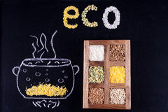 Word ECO composed of groats on black background. Mel drawn pan in which cooked cereal Stock Image